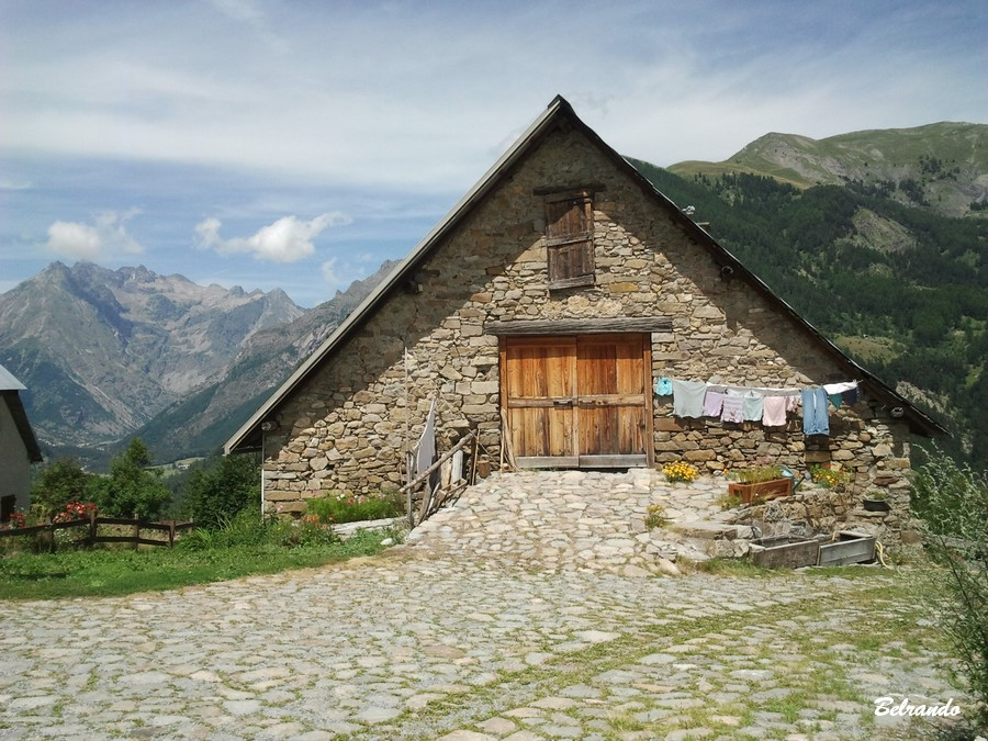 Maison en pierres et au toit plongeant vers le sol